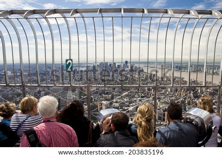 NEW YORK, USA - SEPTEMBER 8: tourists on the observation deck at the Empire State Building view at the New York City Skyline, New York City, United States of America, sept 8 2011 - stock photo