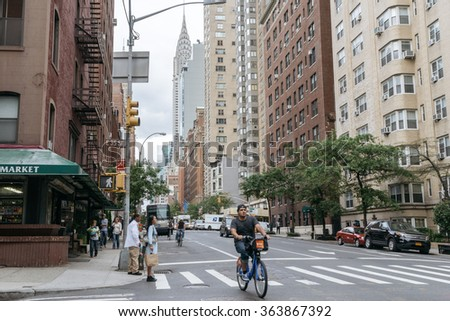 New York, USA - September 22, 2015:  Yellow taxi and people on the street of New York. Chrysler building is one of the main symbols of New York.