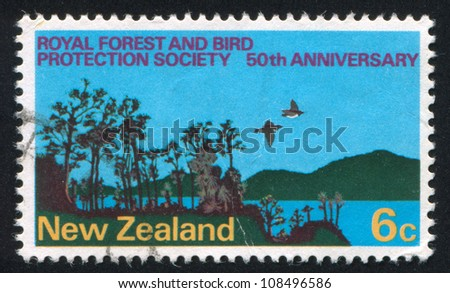 NEW ZEALAND - CIRCA 1973: stamp printed by New Zealand, shows Forest, Birds and Lake, 50th anniversary of Royal Forest and Bird Protection Society, circa 1973 - stock photo