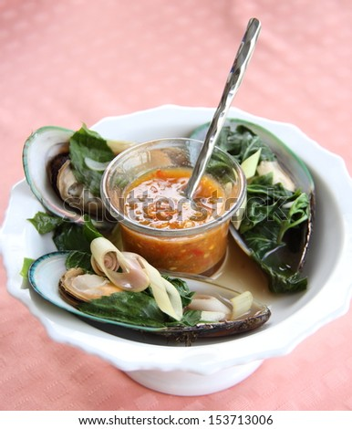 New Zealand green mussels on white plate with seafood sauce - stock photo