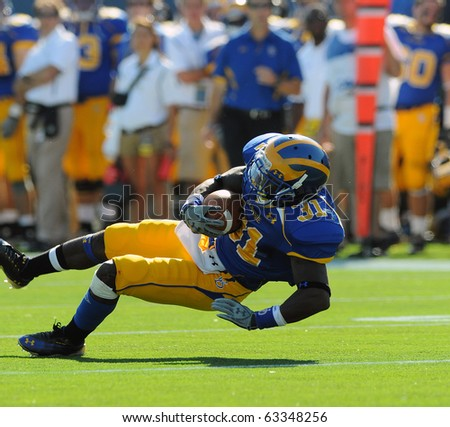 NEWARK, DE - OCTOBER 9: University of Delaware wide receiver Phillip Thaxton falls to the ground with the ball after a tackle in a game against Maine October 9, 2010 in Newark, DE. - stock photo