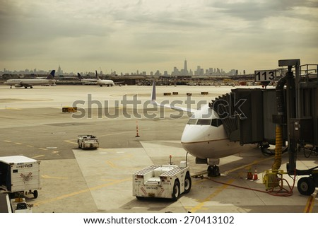 NEWARK, NJ - MAY 11: Airplane at airport with New York City skyline on May 11, 2014 in Newark, New Jersey. Newark airport is 10th busiest in US  - stock photo
