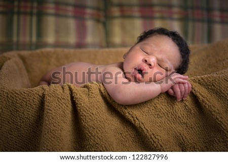 Newborn African American Boy Closeup Sleeping in Basket with Brown Blanket, Shallow Depth of Field - stock photo