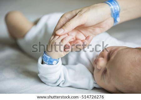 Newborn and his mom with name tag bracelets, first days of life