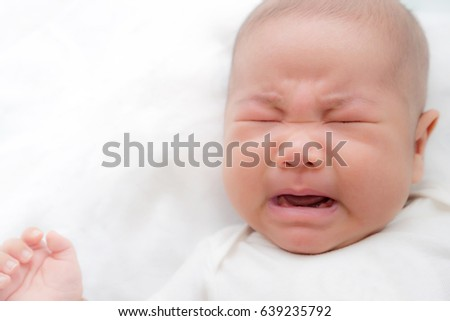 Newborn Asian baby crying on bed