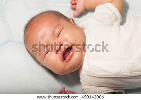 Newborn Asian baby girl lying and crying on a bed. - stock photo