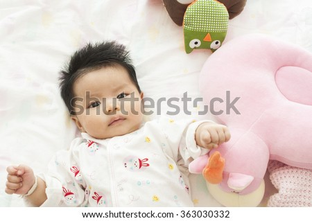 Newborn asian baby girl playing on bed  - stock photo