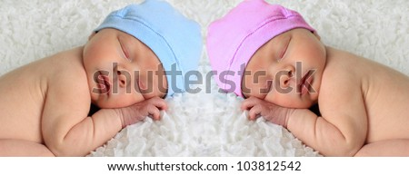 Newborn babies asleep on a white blanket. - stock photo