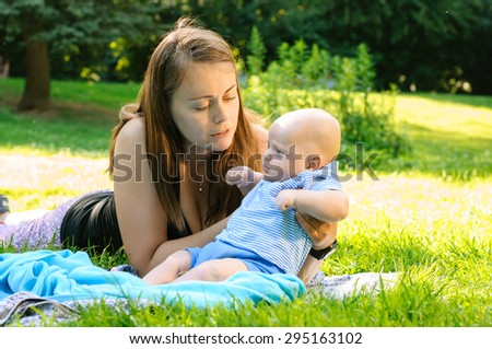 newborn baby and mother in garden on grass