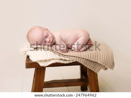 Newborn Baby Asleep, sleeping and taking a nap on a rustic wood chair, posed and curled up - stock photo