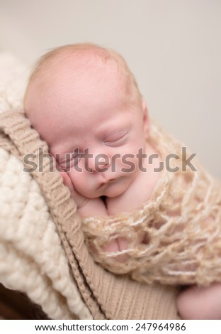 Newborn Baby Asleep, sleeping and taking a nap on a soft knit blanket, posed and curled up - stock photo