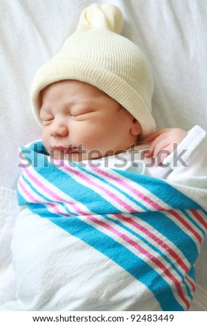 Newborn baby asleep, swaddled in hospital blanket and wearing a hat - stock photo