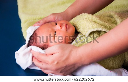 Newborn baby bathing on mothers hands