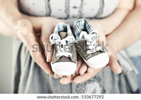 Newborn baby booties in parents hands. Close up. - stock photo