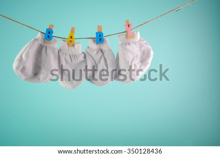 newborn baby bottom bootties hanging on clothesline with clothespins. - stock photo