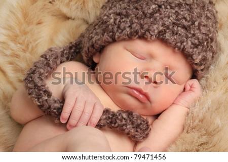 Newborn baby boy asleep on a fur blanket. - stock photo