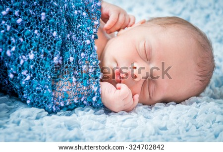 Newborn baby boy asleep wrapped in a blue blanket closeup - stock photo