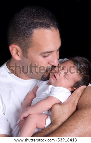 Newborn baby boy being held and kissed by his father - stock photo
