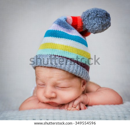 Newborn baby boy 10 day old sleeping in the striped hat - stock photo