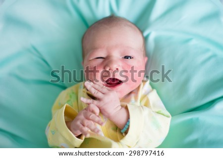 Newborn baby boy in bed. New born child sleeping on a green blanket. Children sleep. Bedding for kids. Infant napping in bed. Healthy little kid shortly after birth. Tired baby yawning. - stock photo
