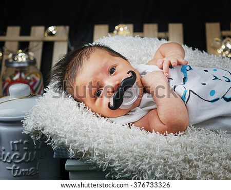 Newborn Baby Boy Laying Down Wearing Mustache Pacifier - stock photo