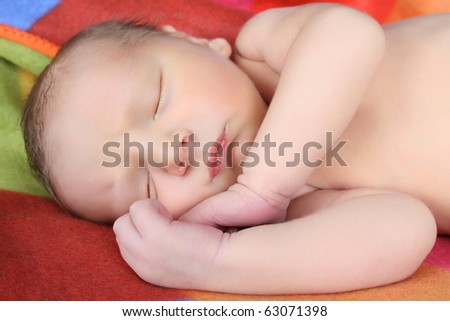 Newborn baby boy lying on a colorful blanket - stock photo