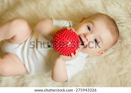 newborn baby boy playing with a red ball - stock photo