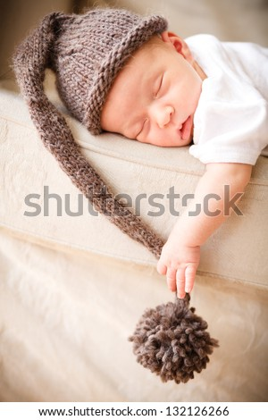 Newborn baby boy resting on a couch - stock photo