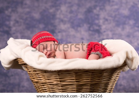 Newborn baby boy sleeping on a white blanket in a wicker basket. Infant is wearing a red knit cap and diaper cover. Soft focus with a shallow depth of field with a purple background. - stock photo