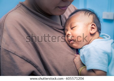 Newborn baby boy sleeping on his mother's chest at home.