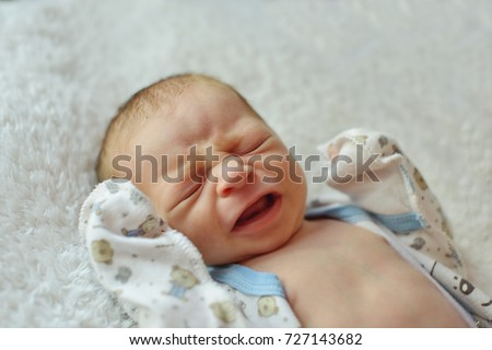 Newborn baby crying and laying on the bed
