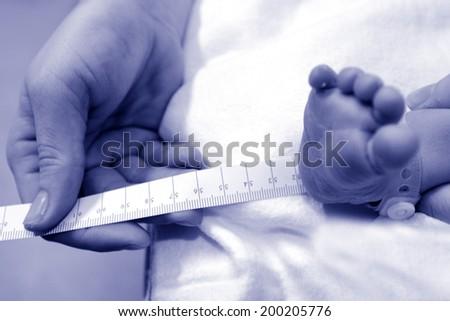 Newborn baby during childbirth examination. - stock photo