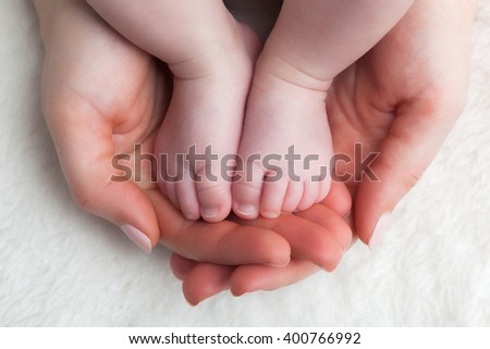 Newborn baby feet in mother's hands. Concept of child care, feeling safe, protect. - stock photo