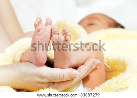 Newborn baby feet in mother's hands with soft yellow blanket - stock photo