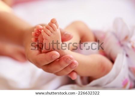 Newborn baby feet in the mother hands - stock photo