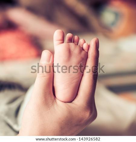 newborn baby feet on female hand - stock photo