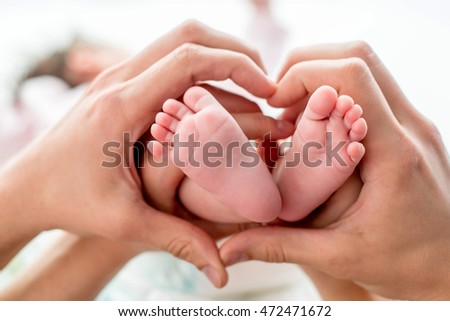 newborn baby feet on mom and dad hands, shape like a lovely heart. happy family concept