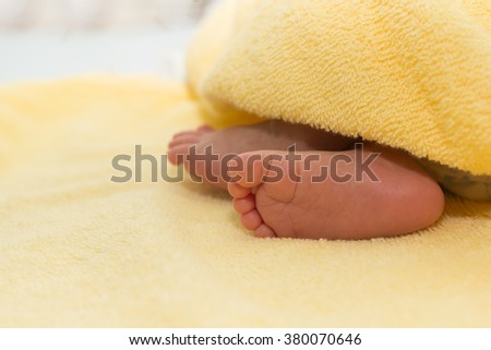 Newborn baby feet on the floor with a soft cloth. - stock photo