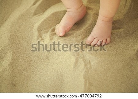 Newborn baby feet playing in the sand in summertime