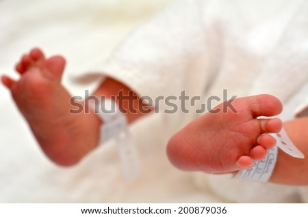 Newborn baby feet with identification bracelet tag name. - stock photo