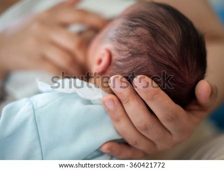 Newborn baby first days drinking breast milk - stock photo