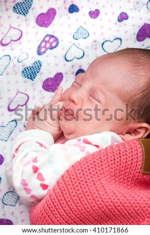 Newborn baby frowning while sleeping in the crib, having colic - stock photo