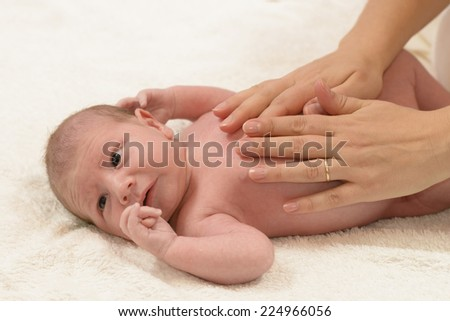Newborn Baby getting oil massage by his mother - stock photo