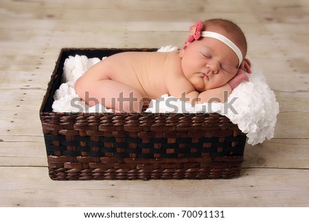 Newborn baby girl asleep in a wicker basket. - stock photo