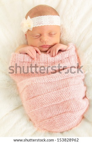Newborn baby girl asleep on a blanket. - stock photo