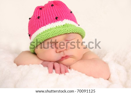 Newborn baby girl, asleep wearing a knitted hat. - stock photo