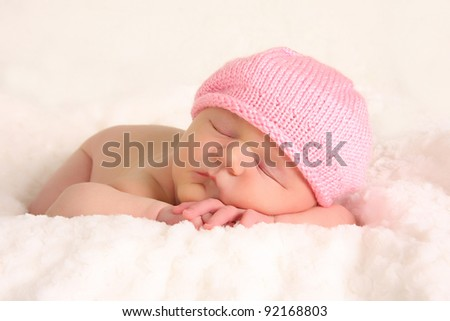 Newborn baby girl in a knitted pink hat. - stock photo
