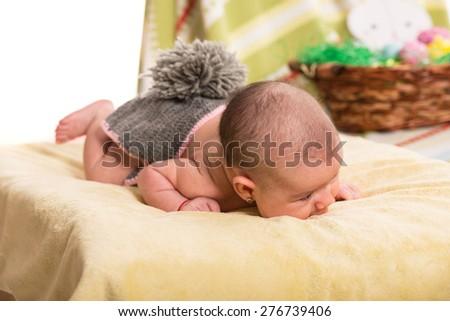 Newborn baby girl in bunny costume laying on yellow blanket - stock photo