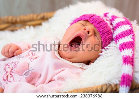 Newborn baby girl in pink knitted hat - stock photo