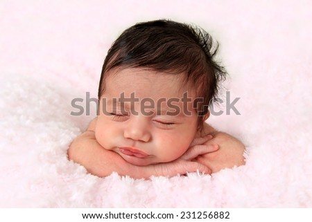Newborn baby girl of Caucasian and Asian heritage wearing a knitted hat. - stock photo